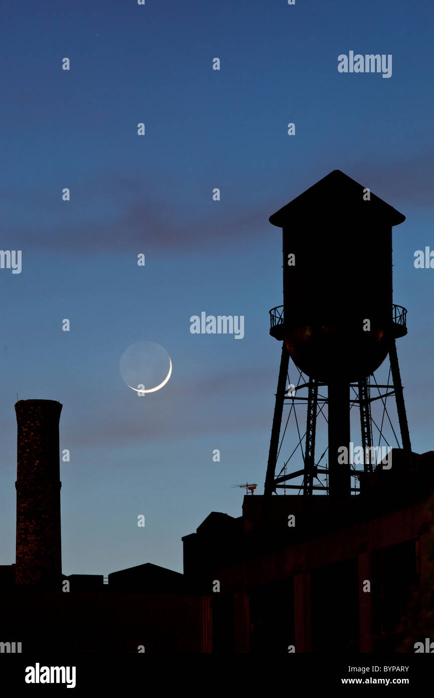 USA, New Jersey, Jersey City, Rooftop water tower and setting crescent moon - Stock Image