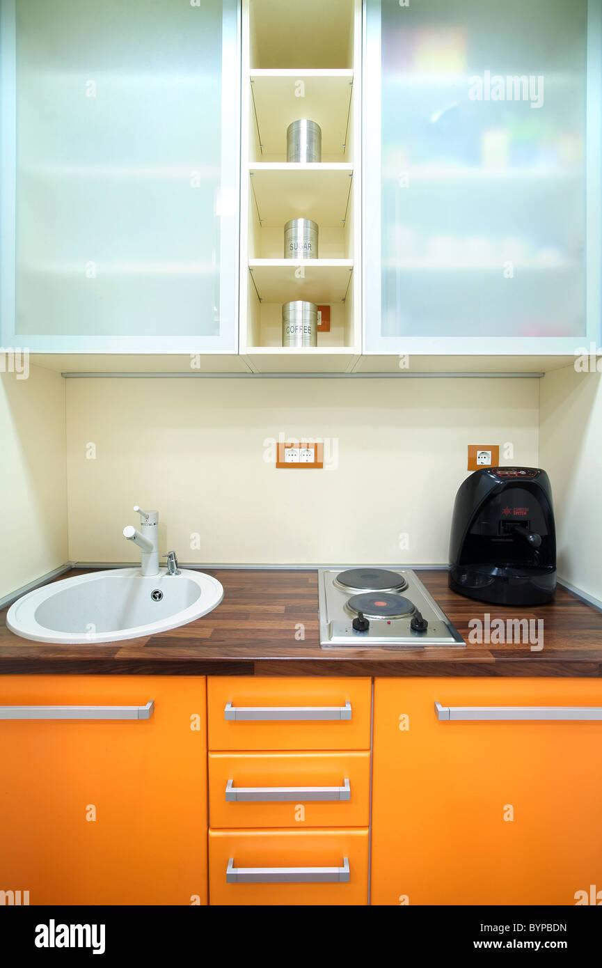 Interior of a small kitchen, orange and white combination of ...