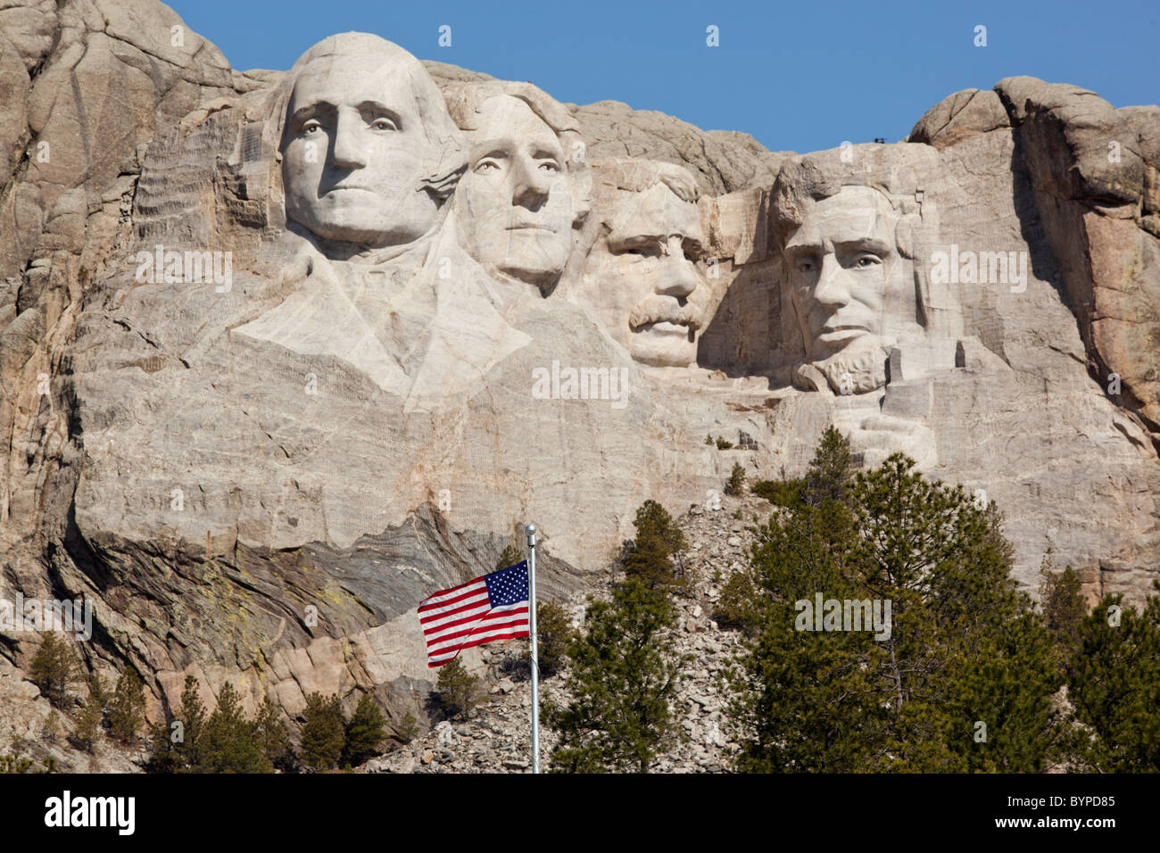 USA, South Dakota, Mount Rushmore National Monument, American flag flies in front of Mount Rushmore carved into Stock Photo