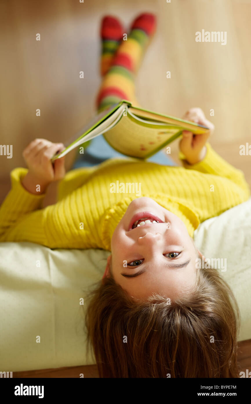 girl lying on bed and reading book - Stock Image