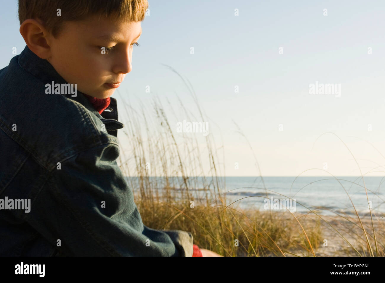 Young boy outdoors contemplatively looking away - Stock Image