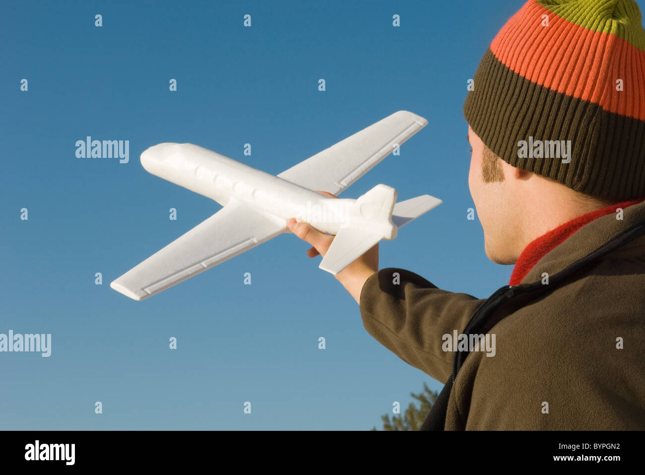 Young man at beach holding aloft toy airplane - Stock Image
