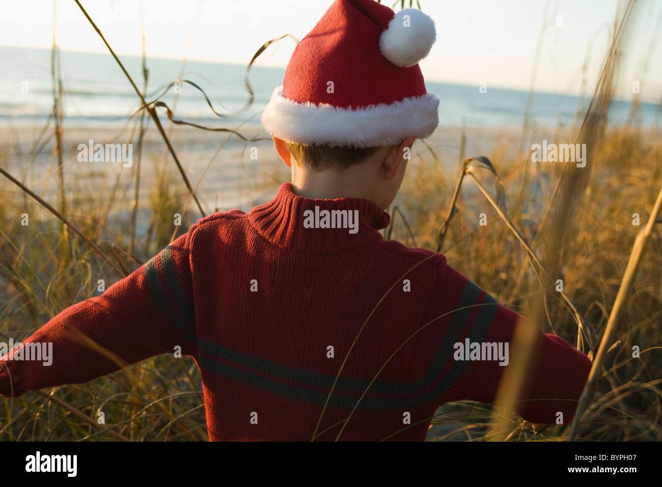 Boy wearing Santa hat exploring outdoors - Stock Image