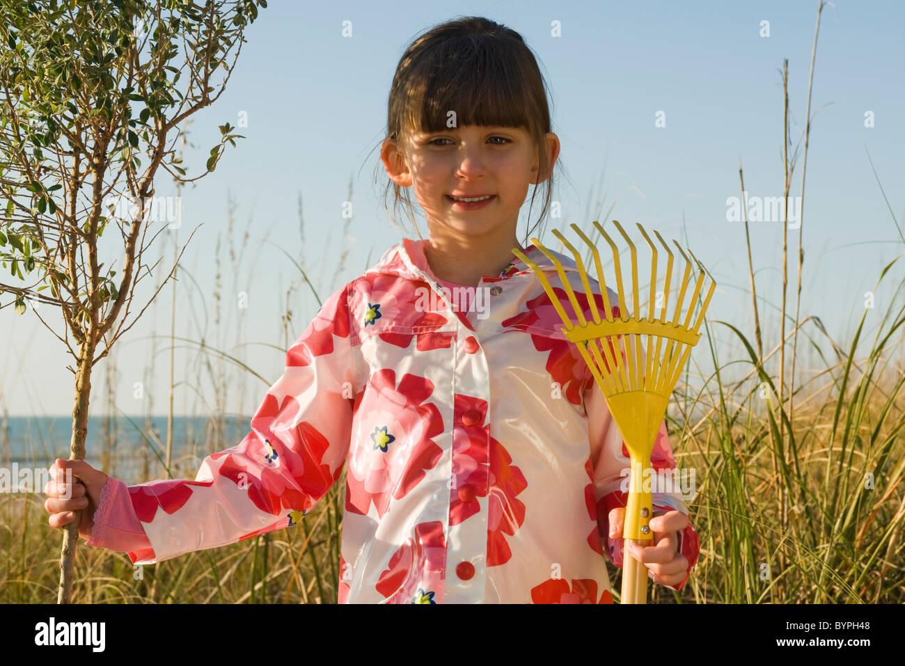 Young girl with gardening rake standing next to tree sapling - Stock Image