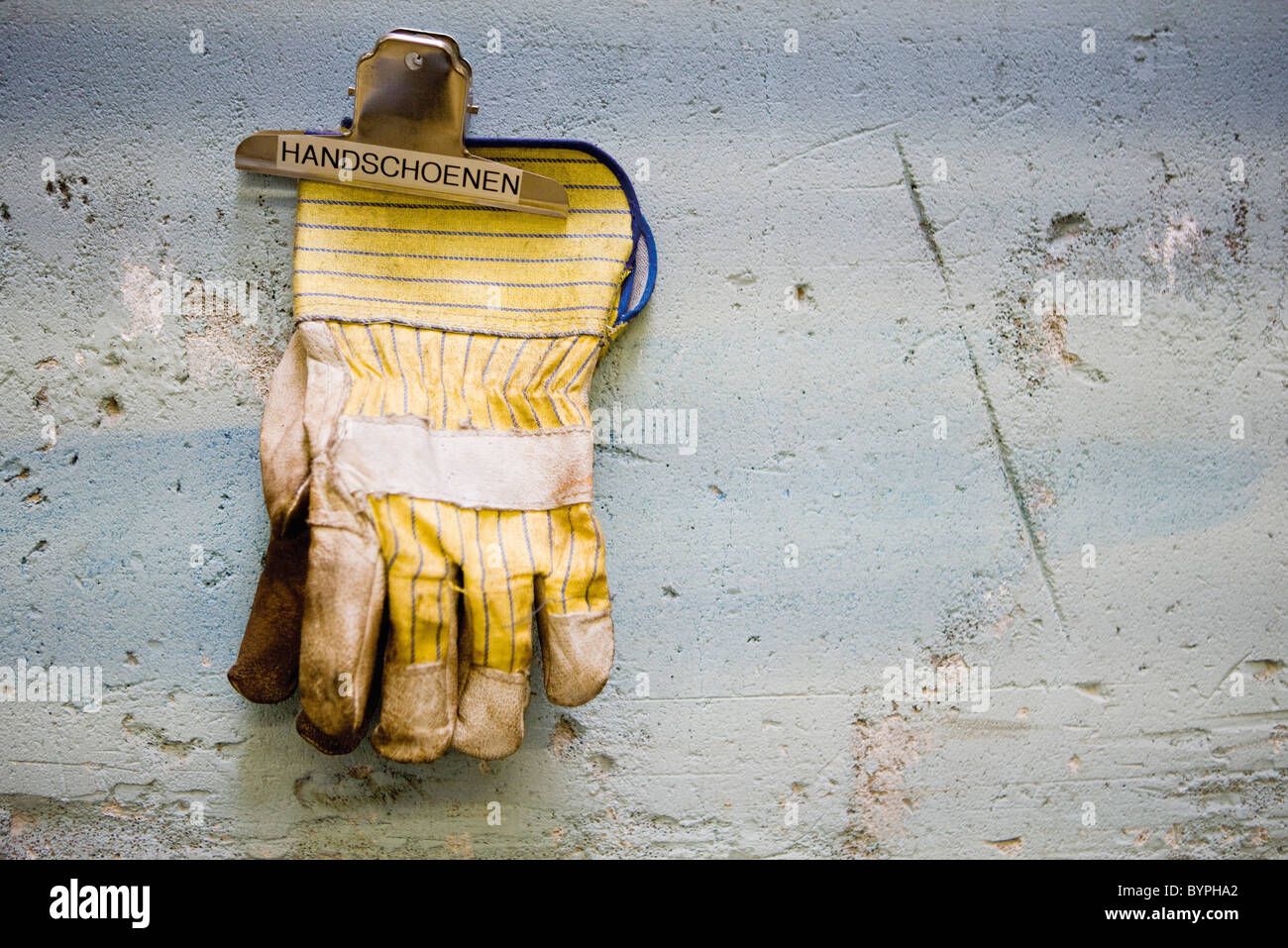 Protective work gloves held up by a binder clip on wall Stock Photo