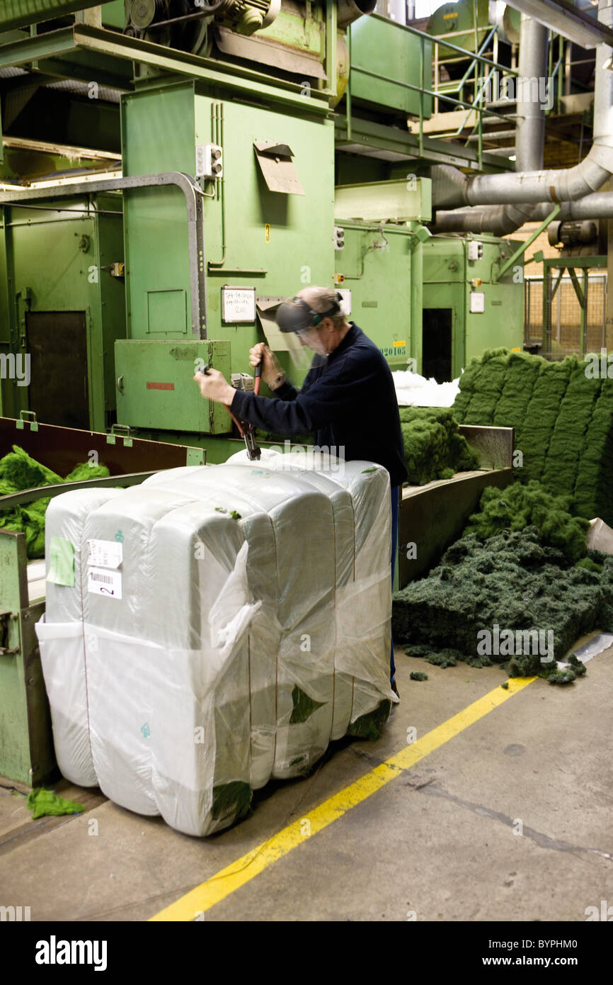 Textile worker unpacking materials in carpet tile factory - Stock Image