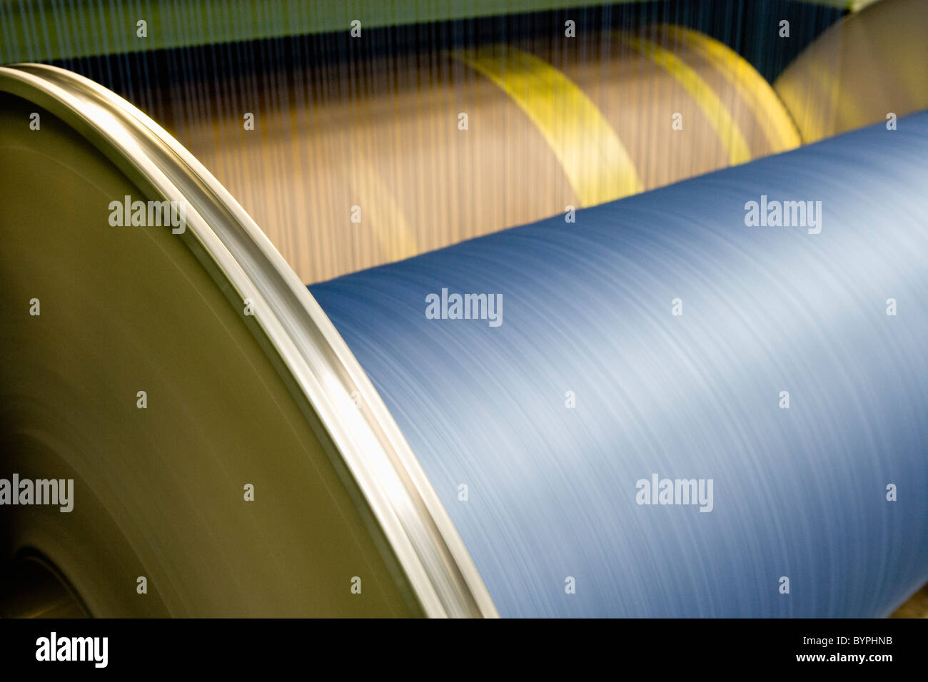 Warp beam of weaving machine loom in carpet tile factory - Stock Image