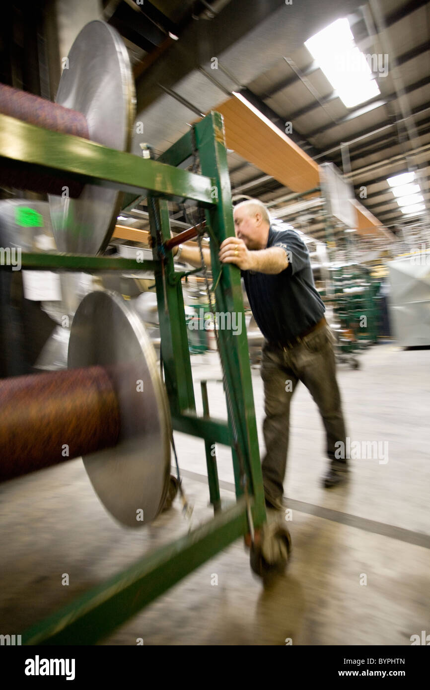 Textile worker setting up warp beams on weaving machine in carpet tile factory - Stock Image