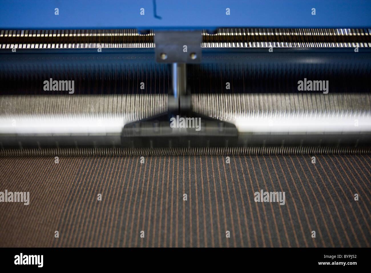 Loom weaving carpet in carpet tile factory - Stock Image