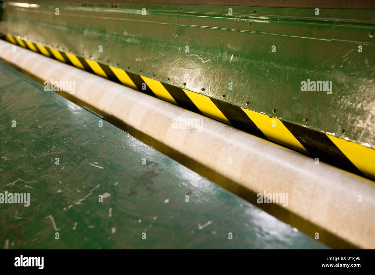 Scuffer machine and empty cardboard roll in carpet tile factory - Stock Image