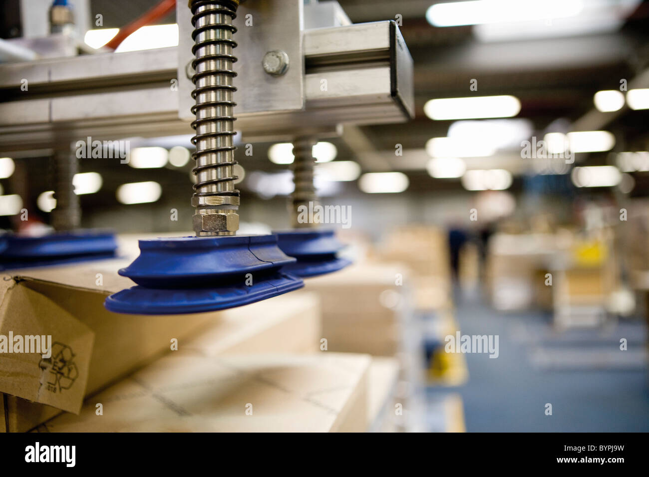 Pneumatic handling robot with technical springs and suction cups designed to lift cardboard boxes in warehouse Stock Photo