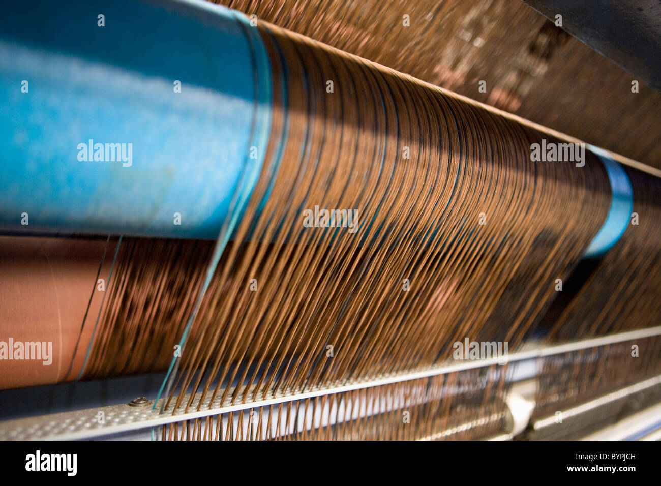 Loom weaving carpet in carpet tile factory - Stock Image