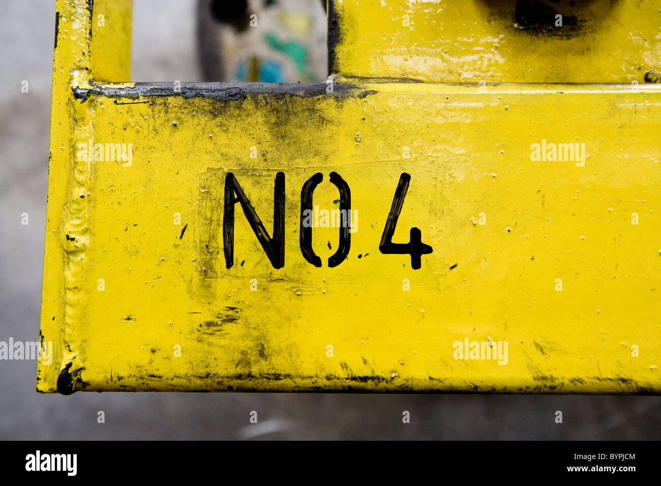 No 4 stenciled on yellow metal surface in factory - Stock Image