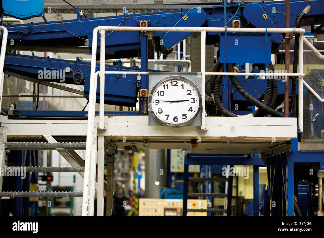 Clock mounted beside metal stairs in carpet tile factory - Stock Image