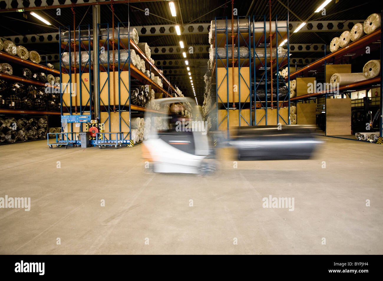 Forklift transporting roll in carpet tile factory warehouse - Stock Image