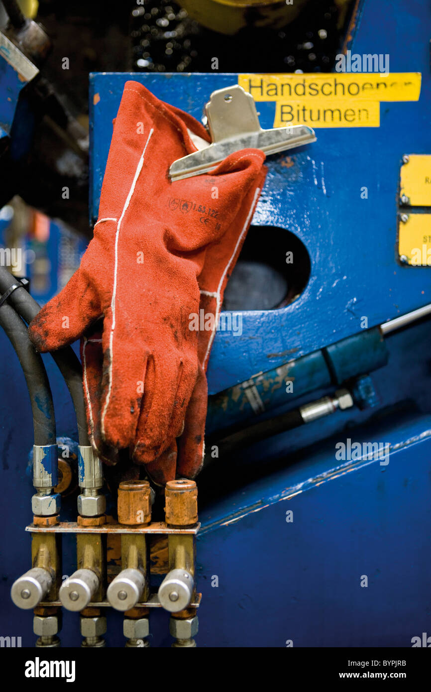 Work gloves stained with bitumen hanging on machine in carpet tile factory Stock Photo