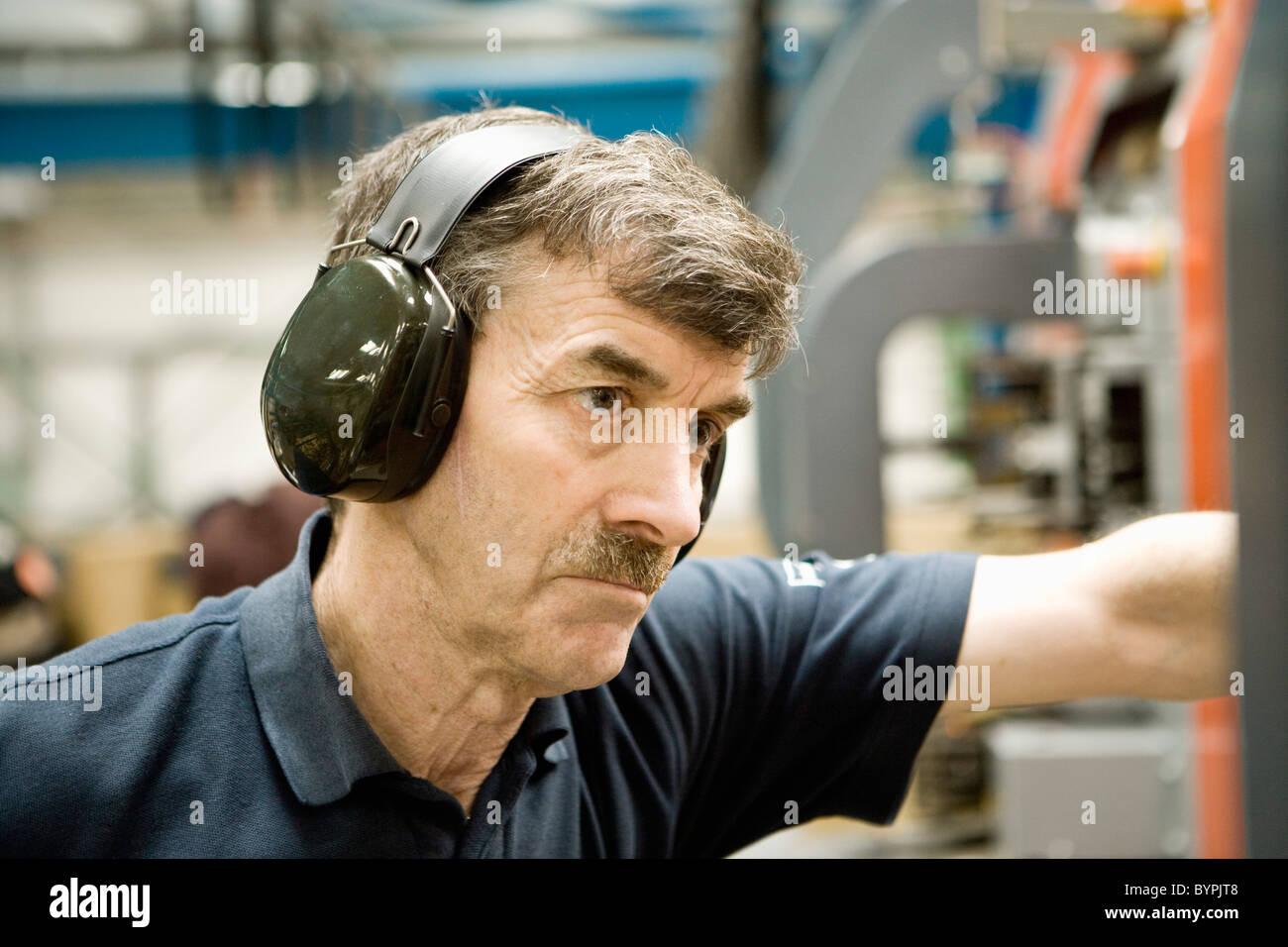 male worker wears headphones - 550×366