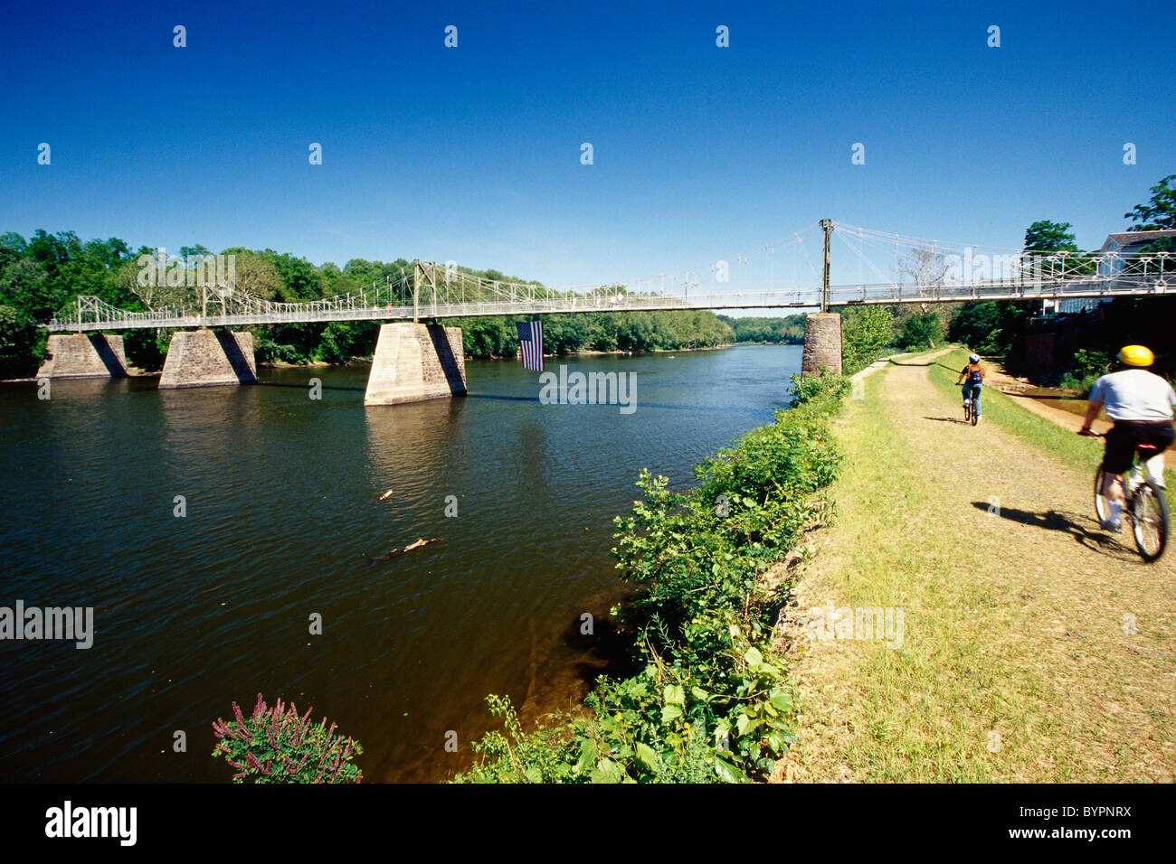 People Bicycling on the Towpath at the Lumberville-Raven Rock Bridge, Pennsylvania - Stock Image