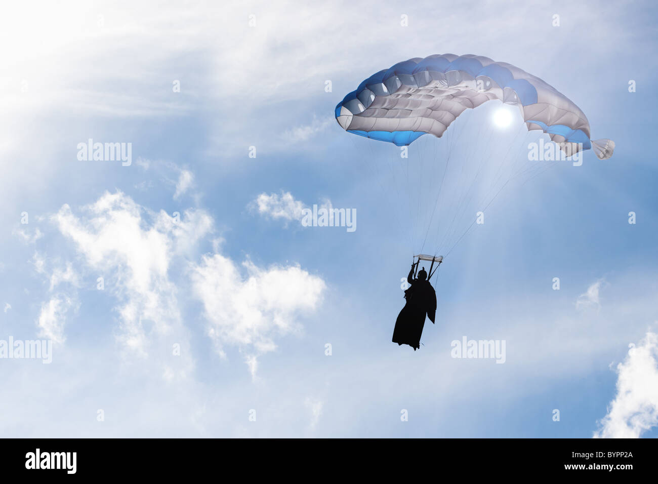 Square parachute canopy in blue sky, in sun rays, inflated, with skydiver silhouette in wingsuit. - Stock Image