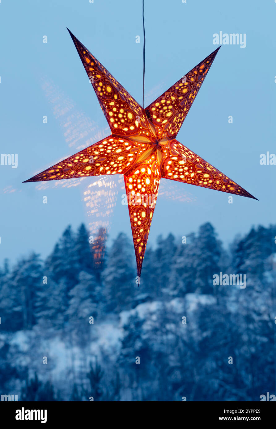 Illuminated night star in a large window - Stock Image