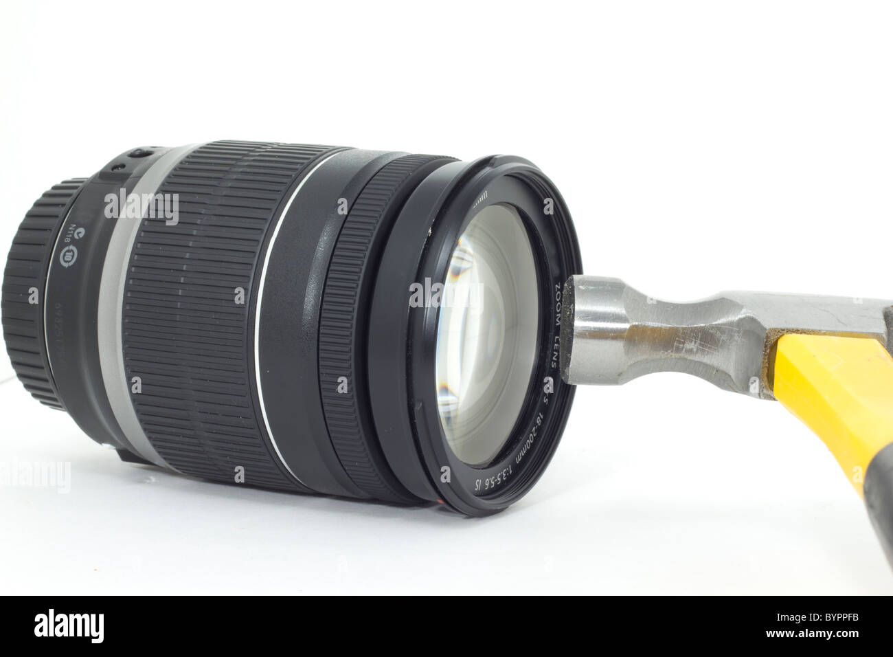 A hammer about to smash a delicate expensive camera lens - Stock Image