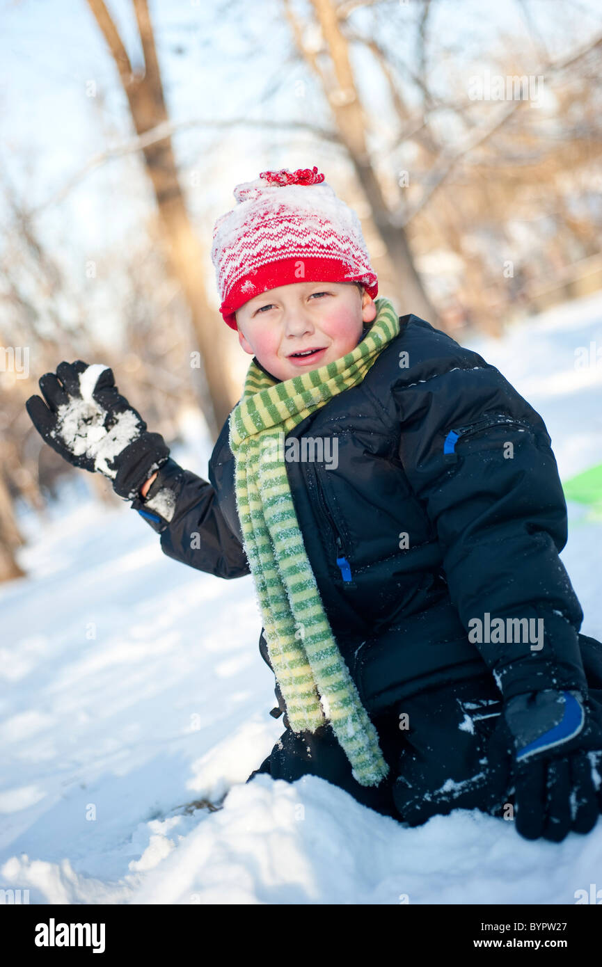 A 4-year-old boy holds a snowball while playing in the snow. - Stock Image