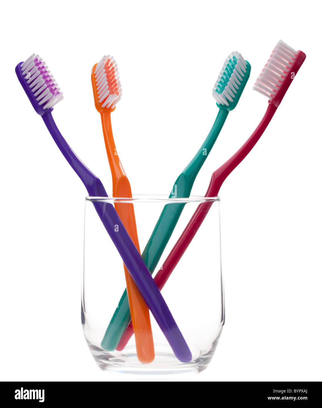 four colorful toothbrushes in a glass, isolated against a white background - Stock Image