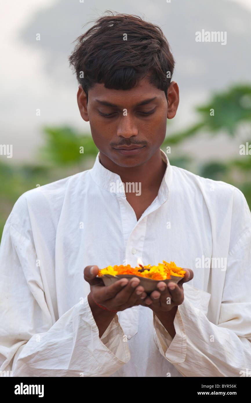 india, Uttar Pradesh, young hindu man holding prayer lamp and marigolds - Stock Image