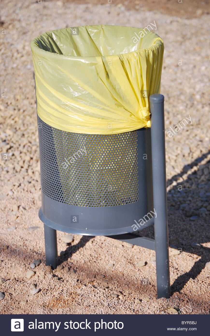 Urban trash can with a yellow bag. Street furniture Stock Photo