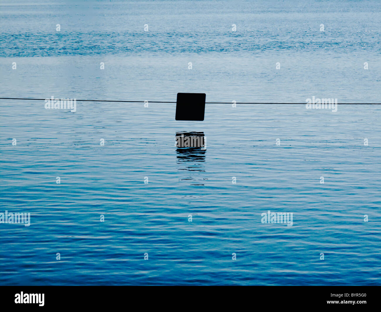 A still body of water with sign - Stock Image