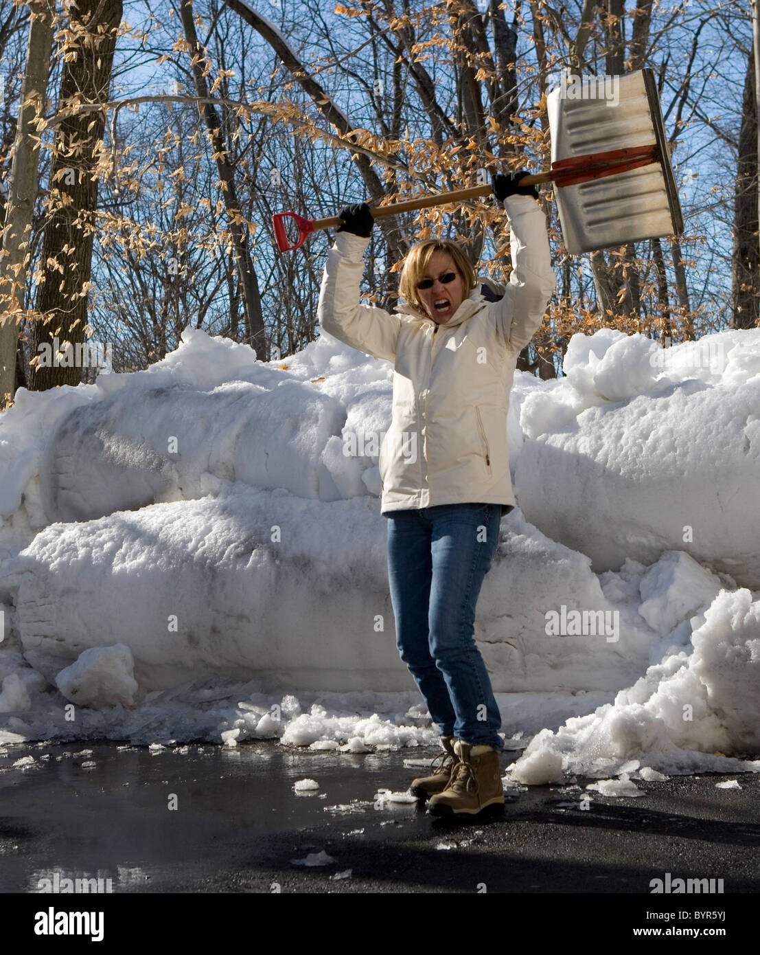 Woman with snow shovel over head in defiance of winter - Stock Image