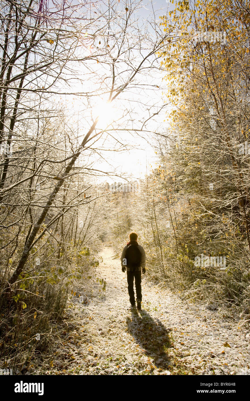 woman walking along an icy path in bright sunlight; thunder bay, ontario, canada Stock Photo