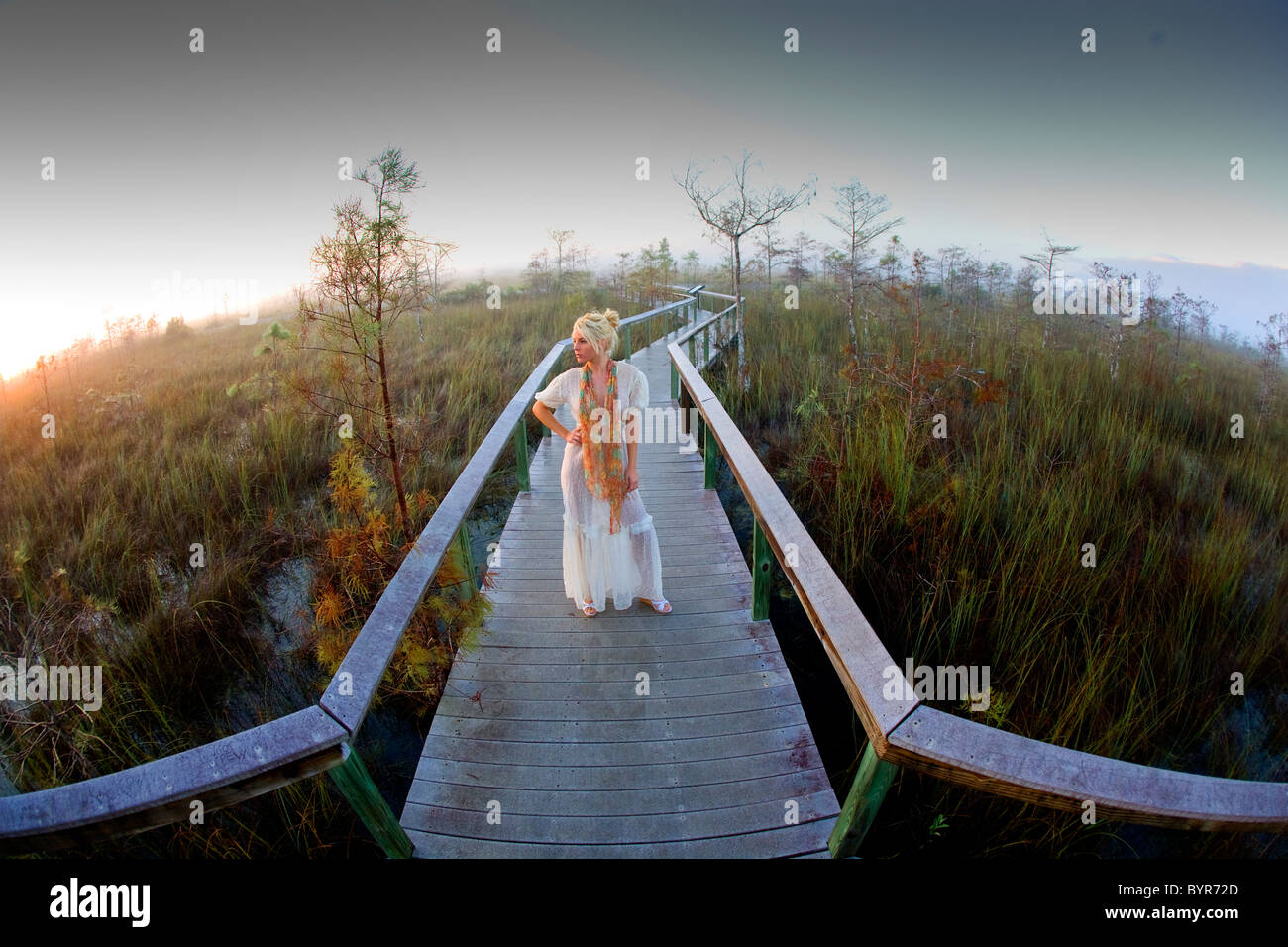 Young woman in fashionable dress standing on wooden walkway in nature - Stock Image