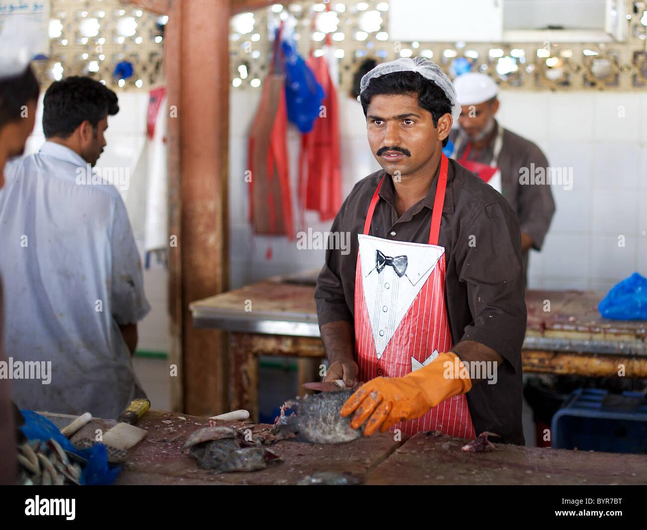 Cleaning fish at Sharjah fish market, Dubai, UAE Stock Photo