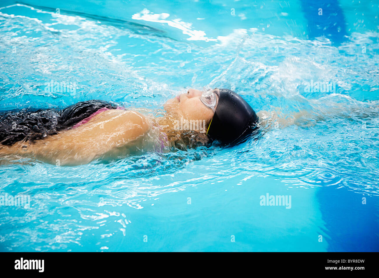 a woman wearing a cap and goggles swims the back stroke; edmonton, alberta, canada - Stock Image