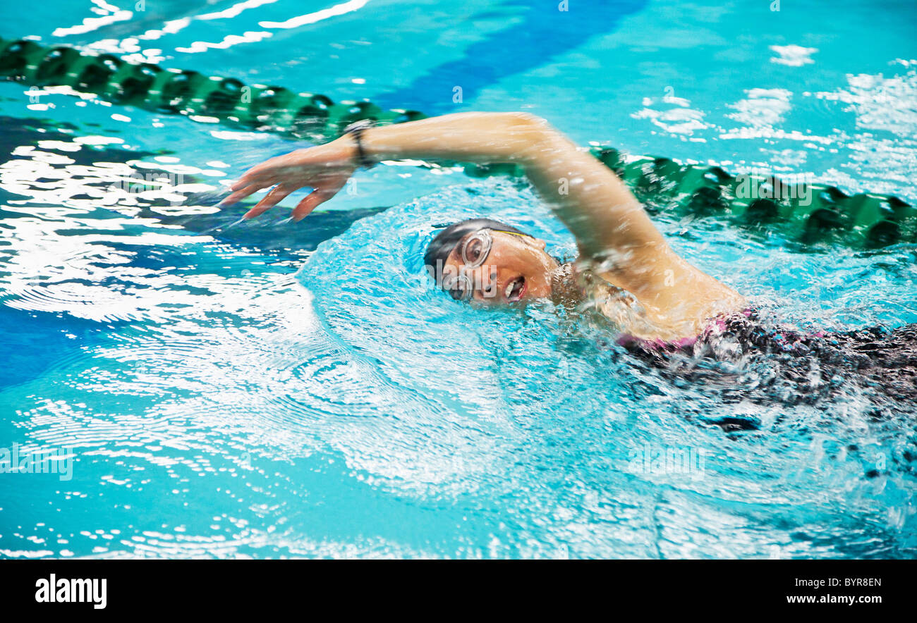 a woman wearing a cap and goggles swims the front stroke in a lane at a swimming pool; edmonton, alberta, canada - Stock Image