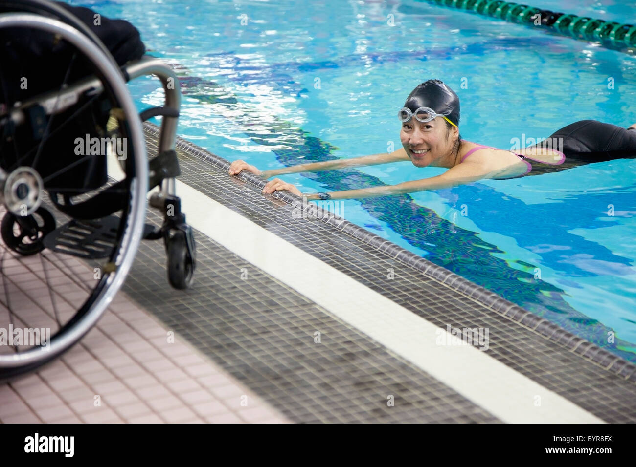 a paraplegic woman swims in a pool with her wheelchair at the water's edge; edmonton, alberta, canada - Stock Image