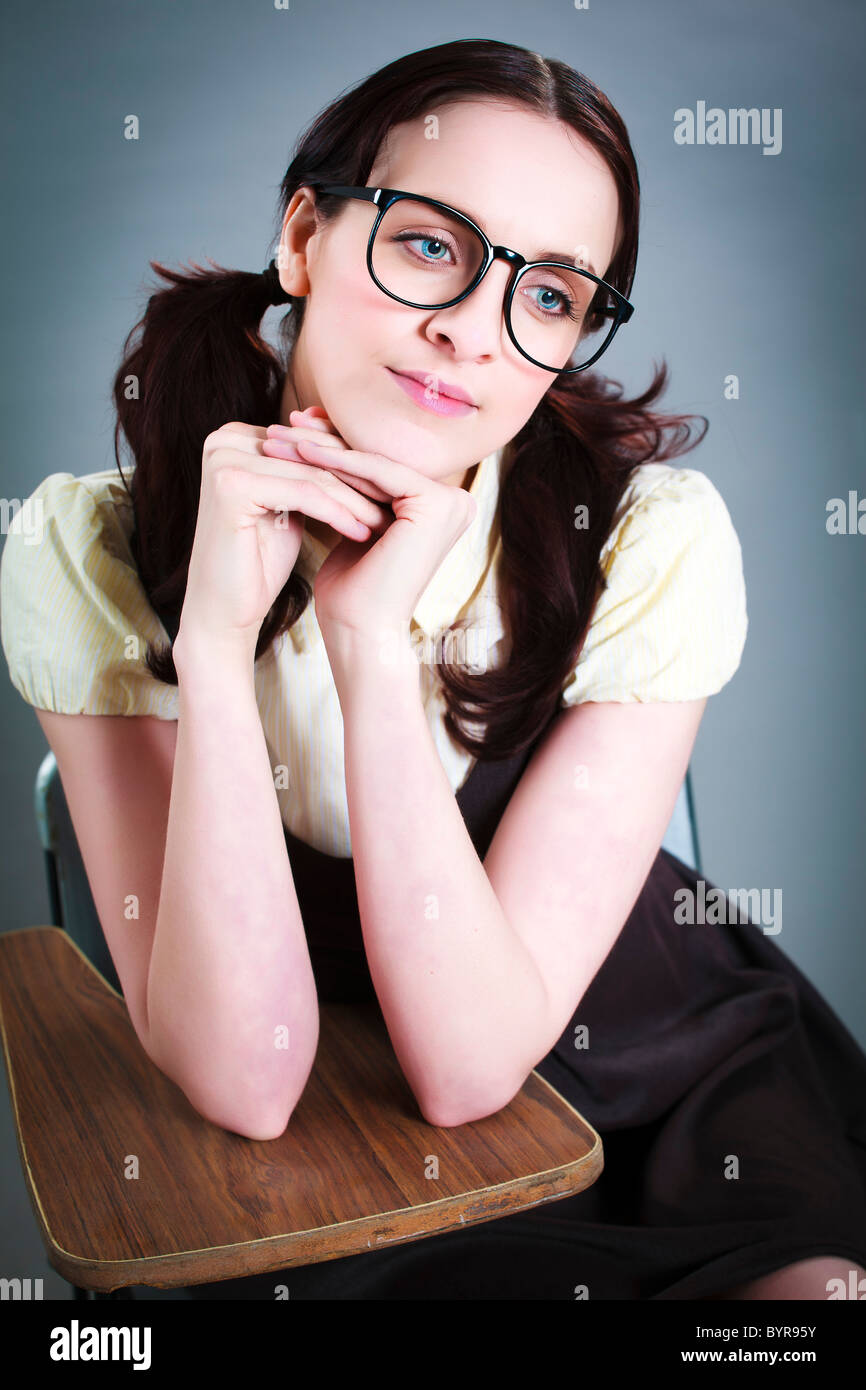 thoughtful geeky girl sits at her desk - Stock Image