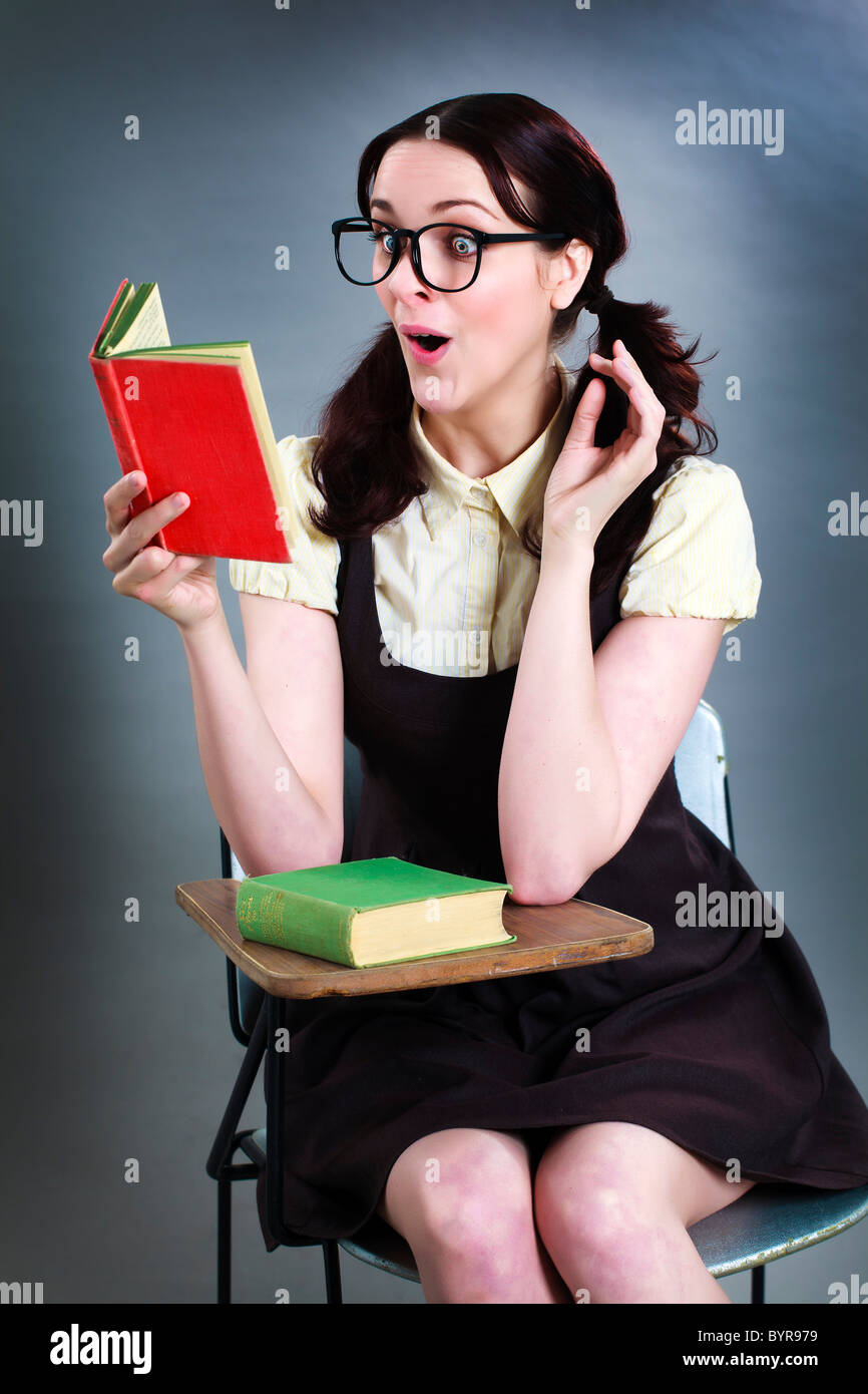 surprised geeky school girl reading at desk - Stock Image