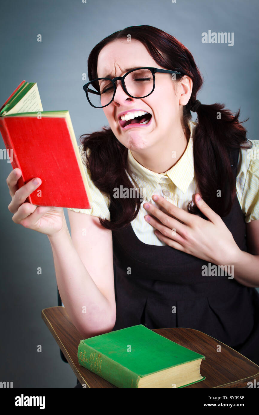 geeky girl reads her book whilst crying uncontrollably - Stock Image