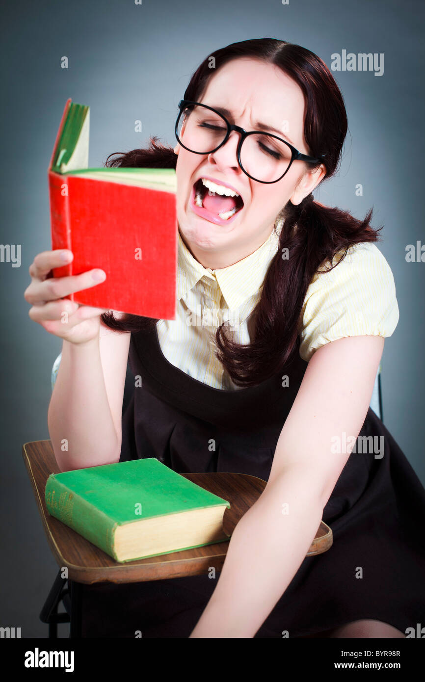 geeky girl reads her book whilst dramatically crying - Stock Image