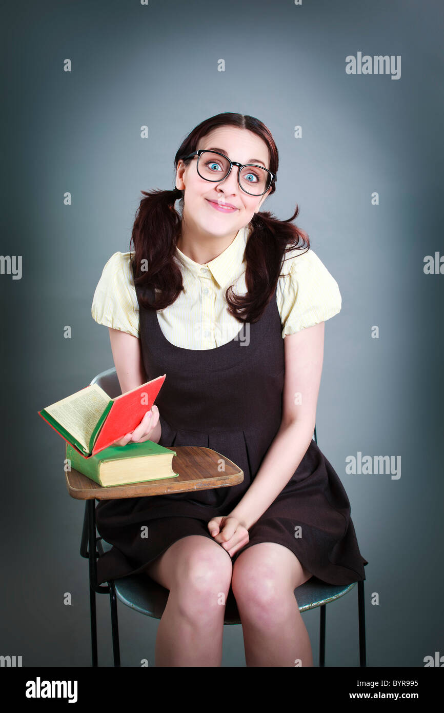 geeky school girl looks up from reading her book with wide eyed half smile - Stock Image