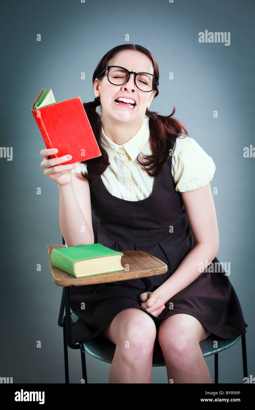 geeky school girl dramatically crying whilst reading at desk - Stock Image