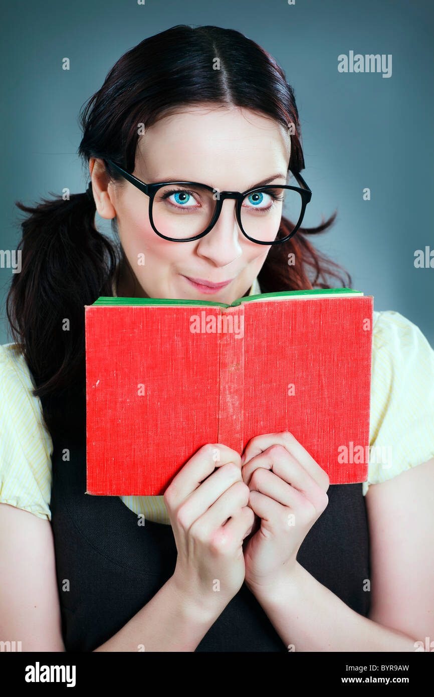 geeky school girl looks over red book - Stock Image