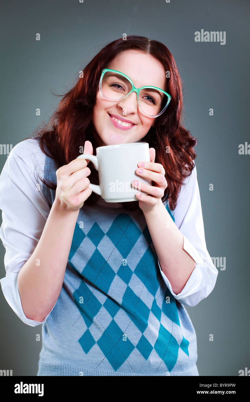 Grinning geeky woman with blank mug - Stock Image