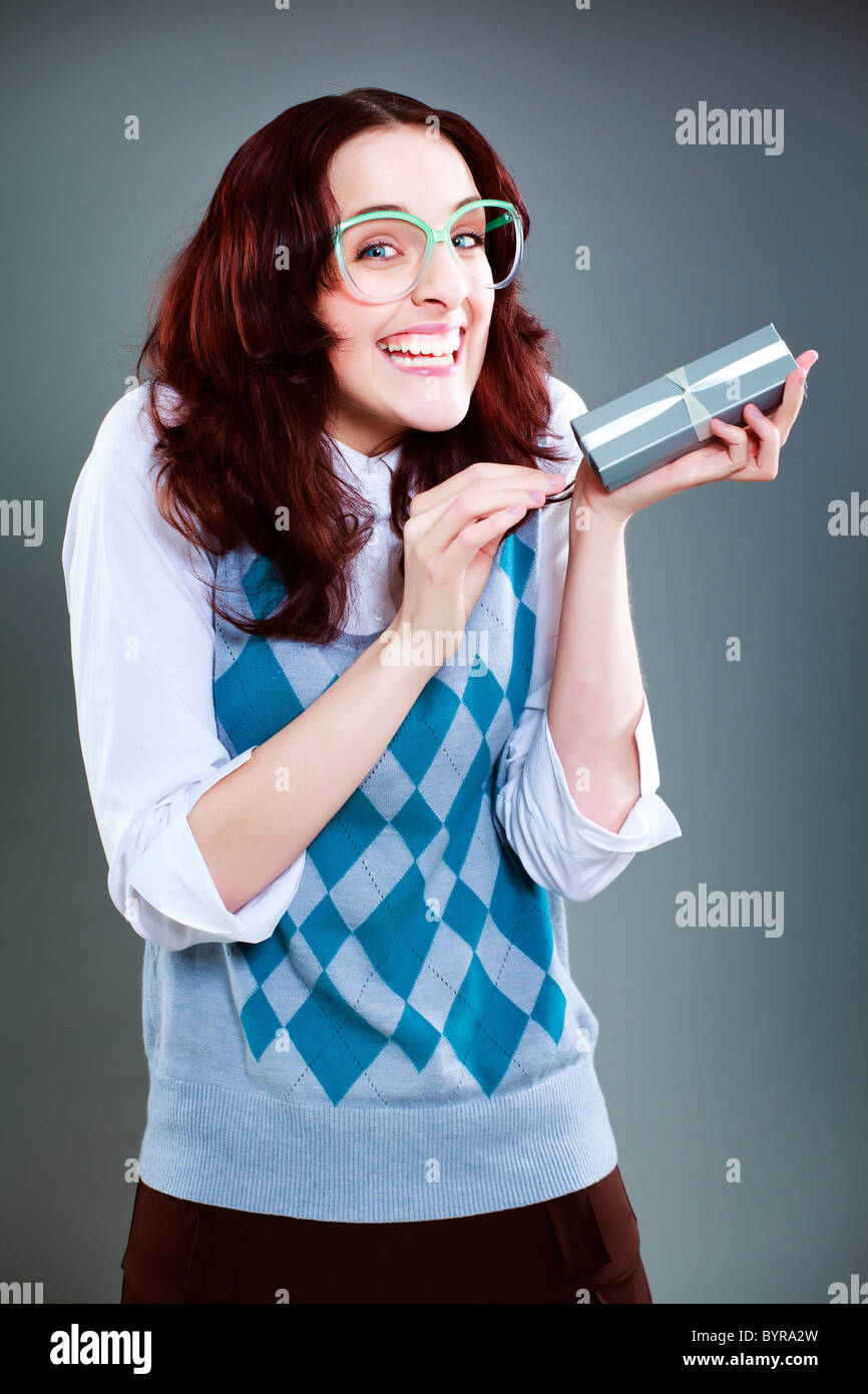 Geeky woman ecstatic with gift box - Stock Image