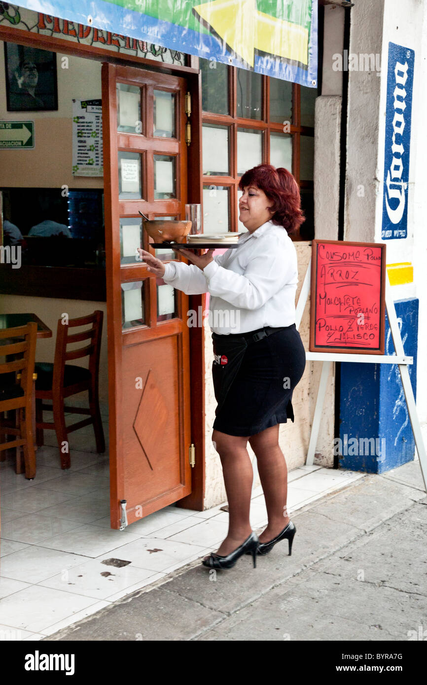curvy red headed mexican waitress in short skirt & stilettos proudly