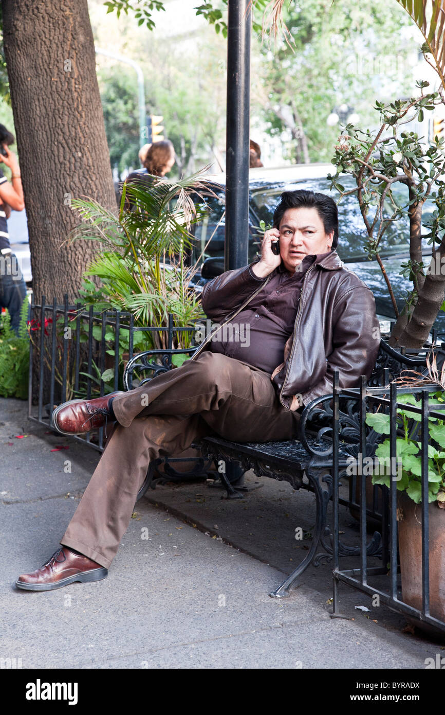 young paunchy Diego Rivera look alike sitting on cast iron bench outside cafe on Avenida Alvaro Obregon talking - Stock Image