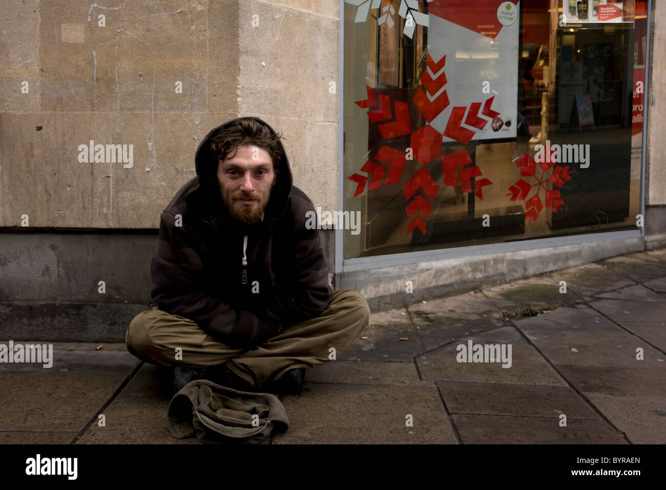 Beggar - a young English male sitting on the High Street behind his cap and next to Christmas decorated shop window - Stock Image