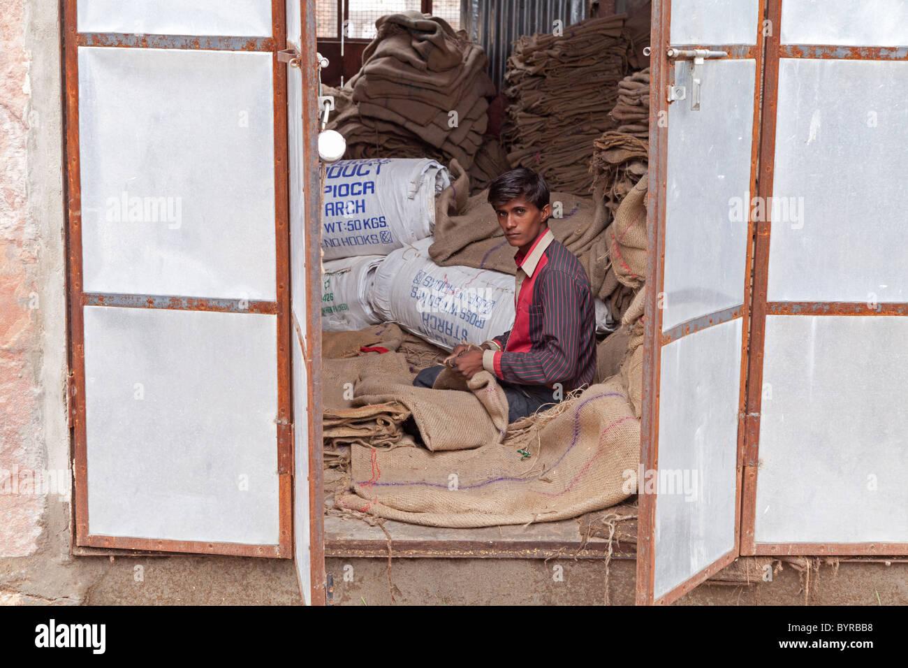 India, Rajasthan, jodhpur young man repairing hessian sacks framed by metal shutters - Stock Image